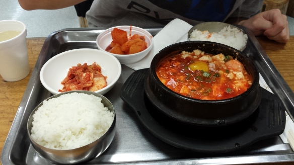 A bowl of soondubu jjigae, rice, banchan