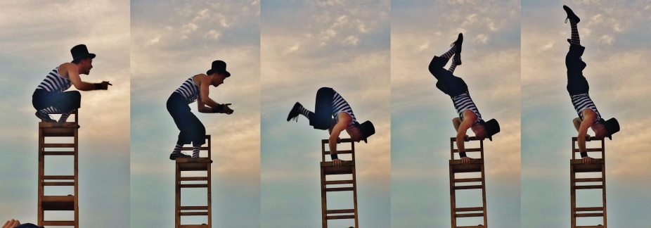 Man in top hap doing a hand stand on chairs
